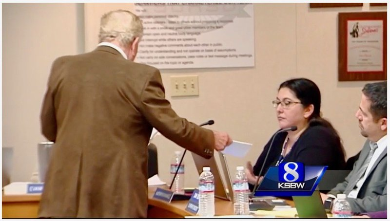 Rick Giffin serves Salinas Union High School District board member Kathryn Ramirez with recall papers.